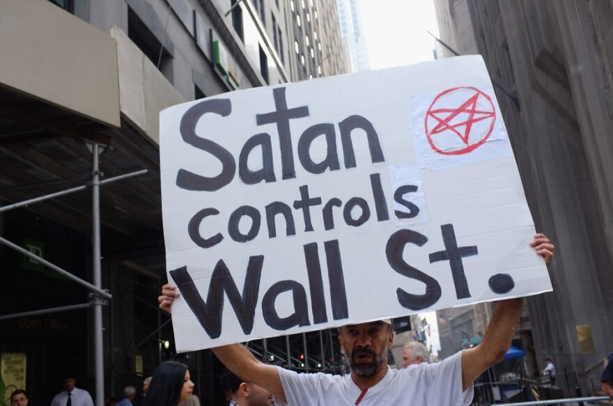 """A demonstrator holds up a sign in front of the  New York Stock Exchange in New York City. Hundreds of activists affiliated with the """"Occupy Wall Street"""" demonstrations have begun living in a park in the Financial District near Wall Street."""