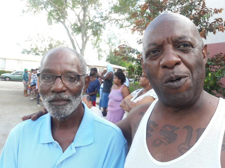 Ronald Kelly, left, stands in line for free ice in Liberty City with his friend Armen Bowlers.