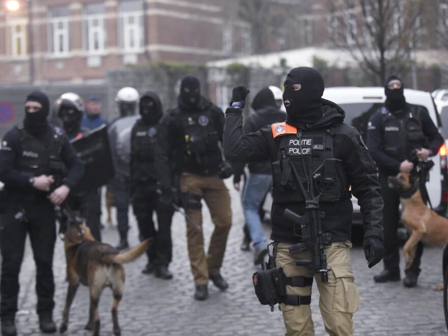 Belgian policemen walk in a street during a police action in the Molenbeek neighborhood in Brussels on Friday.