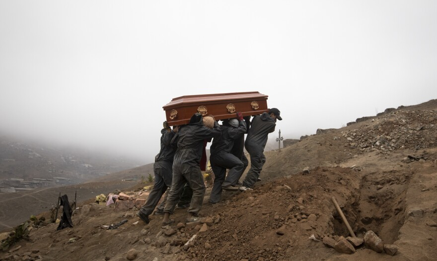 Cemetery workers in Lima, Peru, carry the coffin of a person who died from the coronavirus.