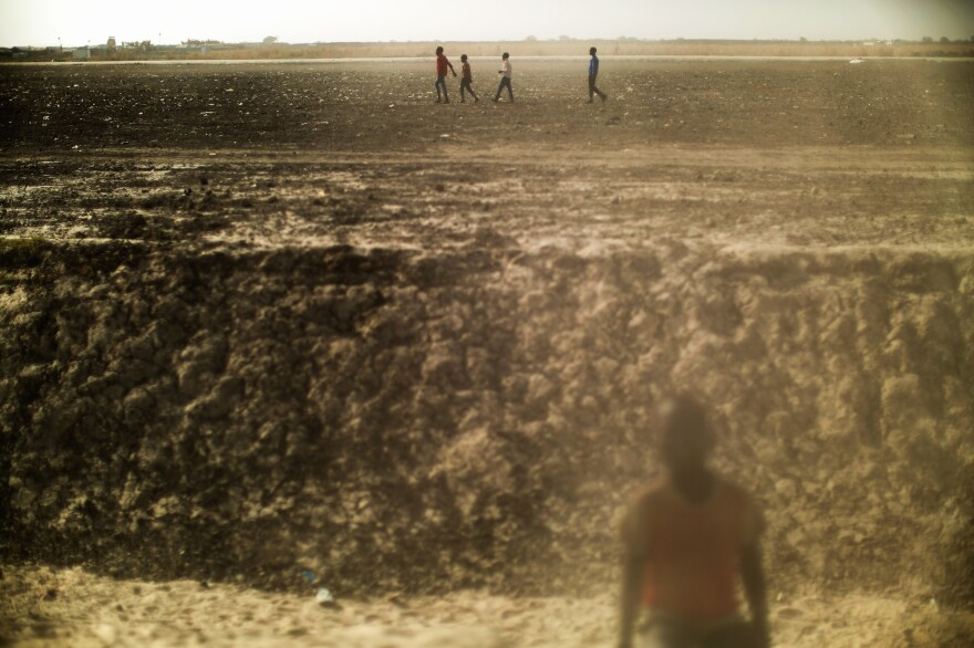 Boys walk across a dusty open plain inside the Protection of Civilians site for displaced people in Bentiu, South Sudan.