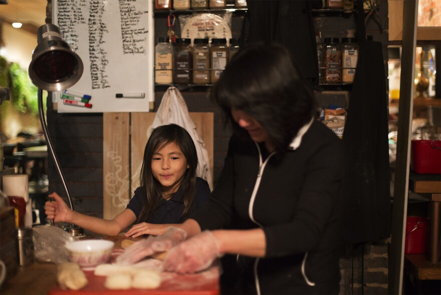 Eight-year-old Alana watches as her grandmother, Phan Ly, demonstrates how she makes pot stickers in the Garden on Grand kitchen on Nov. 14, 2016.