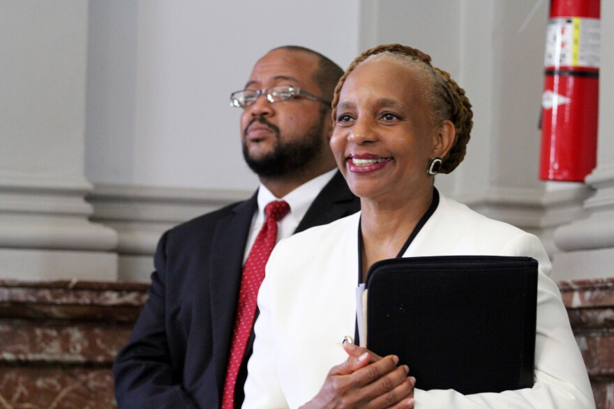 St. Louis License Collector Mavis Thompson watches Friday's Board of Aldermen meeting with aide Bill Ray. Thompson opposes slashing license fees for one or two-person businesses.