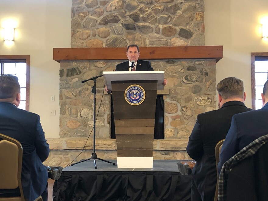 Man stands at a podium with the Utah state seal.