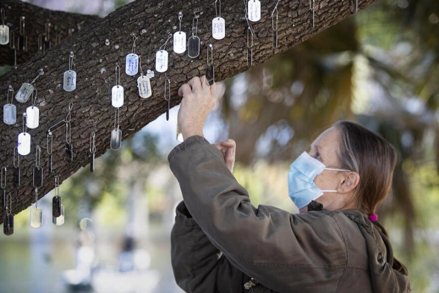 A woman hangs a dogtag on a tree, symbolizing a person experiencing homelessness who died in Austin this year.