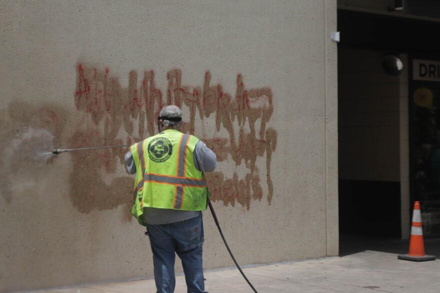 A worker power washes graffiti near a Losoya Street monument.