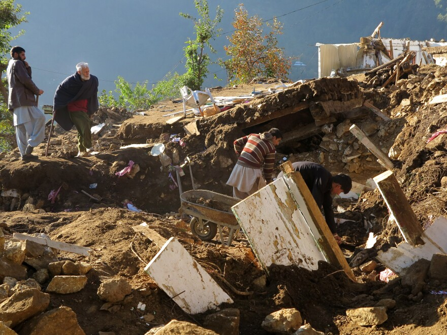 Pakistani villagers dig out their belongings from the rubble of homes destroyed by an earthquake in Shangla in Swat Valley, Pakistan.