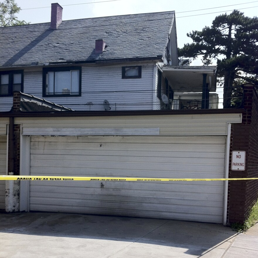 Police tape outside a garage in East Cleveland, Ohio. A woman's body was found inside. Two other victims were also discovered in the neighborhood.