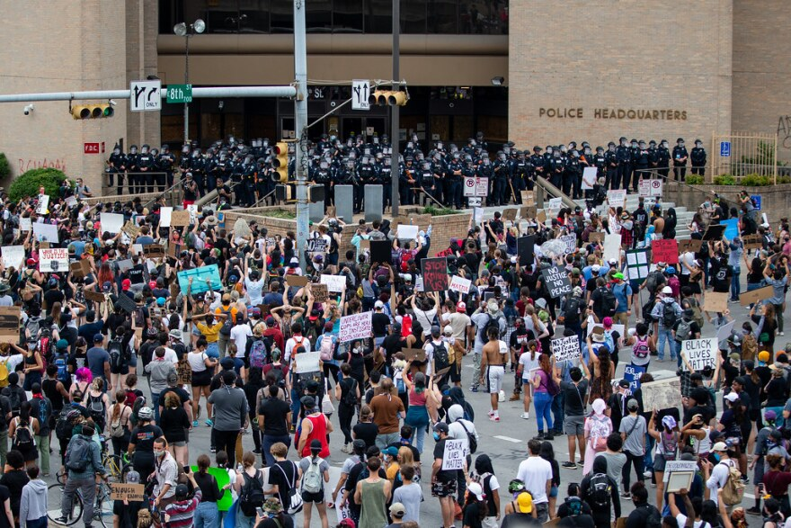 A line of Austin Police officers block the front of police headquarters Sunday as thousands protest in the street.