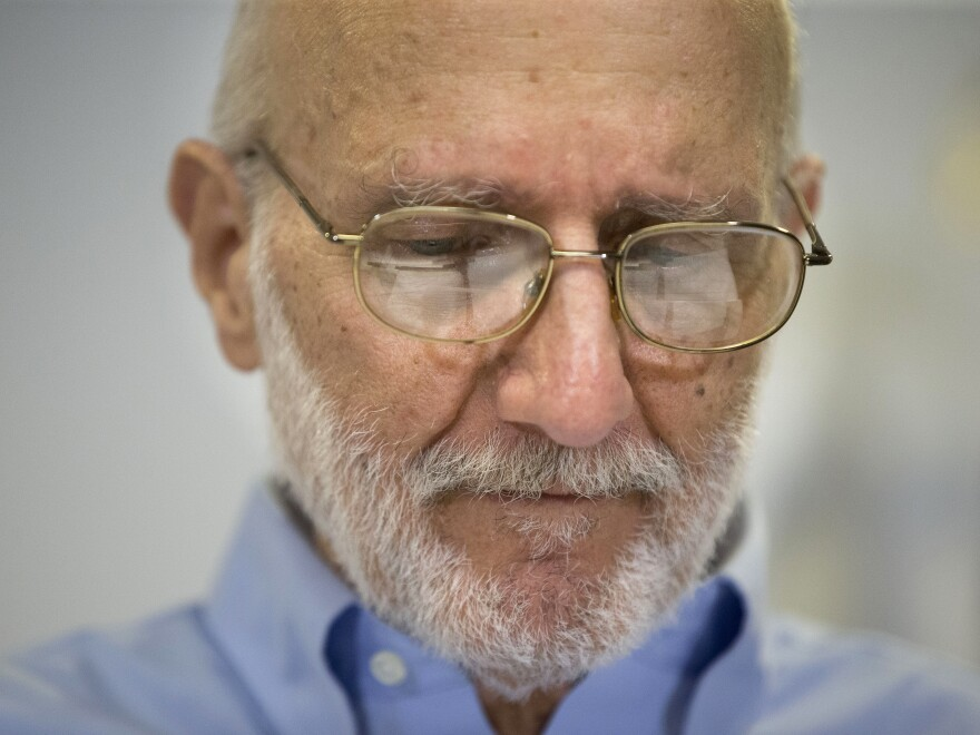 Alan Gross pauses during a news conference at his lawyer's office in Washington on Dec. 17. The federal government will pay him $3.2 million as part of a settlement with the company that employed Gross when he was arrested in Cuba in 2009.