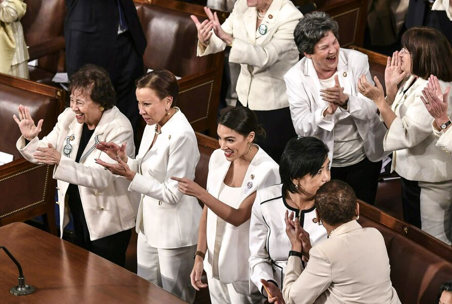 Democratic women, dressed all in white in honor of suffragettes, react as President Trump notes the record number of women in Congress.