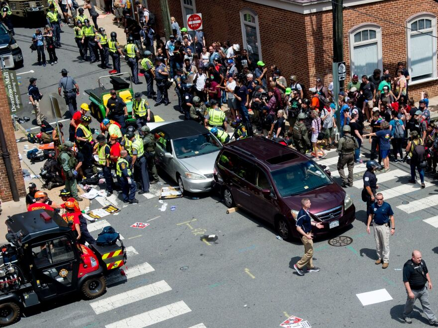 People receive first-aid after a car ran into a crowd of protesters in Charlottesville, Va., on Aug. 12, 2017. Terrorism researchers say right-wing extremists are turning cars into weapons in response to the ongoing protests against police misconduct.