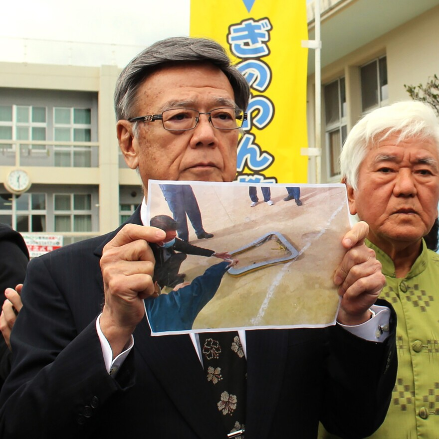 Okinawa Governor Takeshi Onaga, stands outside an elementary school as he shows a picture of the window fallen from U.S. military helicopter onto the sports ground of the school in Ginowan, Okinawa, on Wednesday.