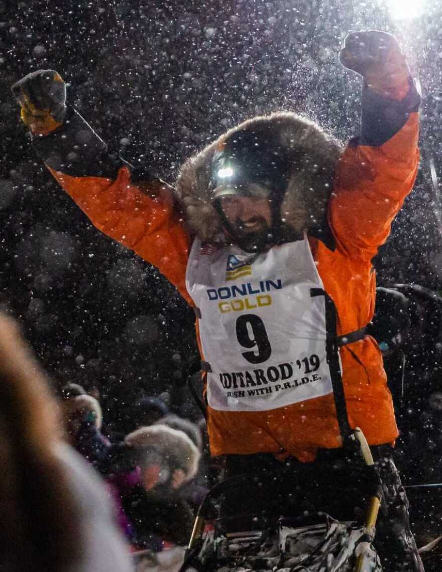 Peter Kaiser celebrates his first-place victory at the finish line of the Iditarod race.