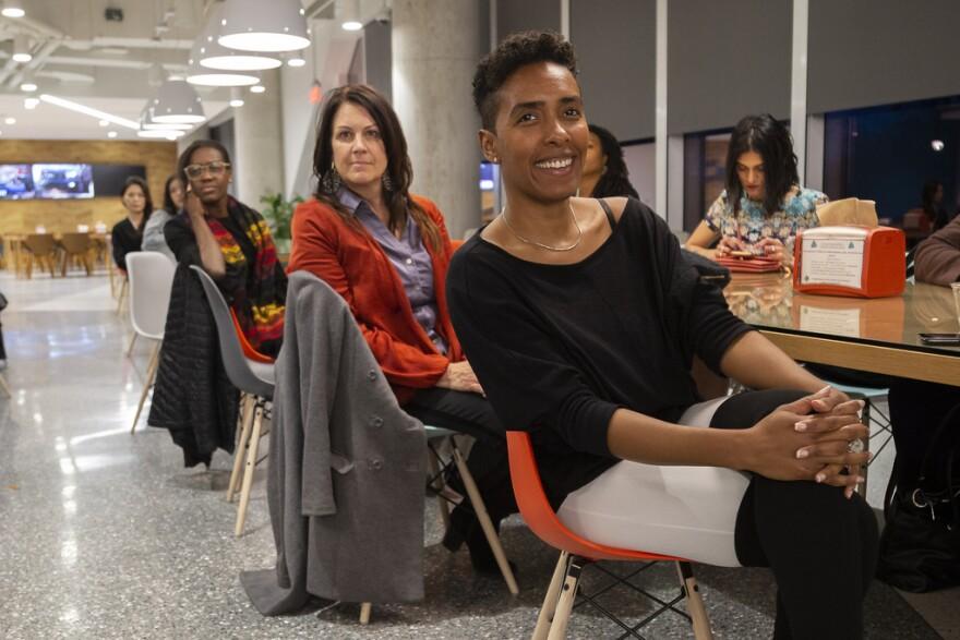 Women attending DivInc Startup Sistas Happy Hour listen to CEO Preston James.
