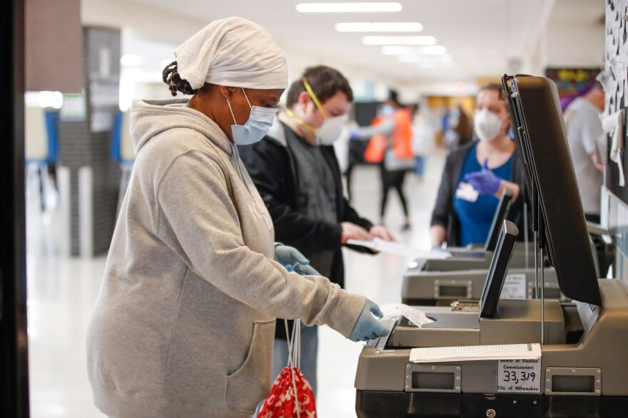 A woman casts her ballot at a high school in Milwaukee this week. The coronavirus pandemic will likely reshape how Americans vote and even who casts a ballot this November.