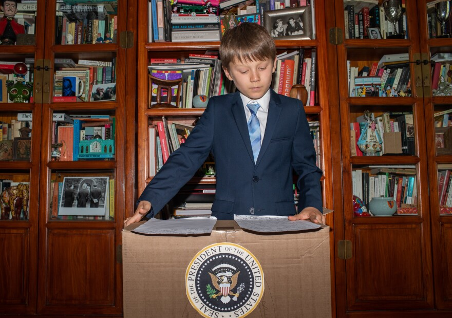 Ben, 10, revises his notes on the Gettysburg Address from a presidential cardboard podium.