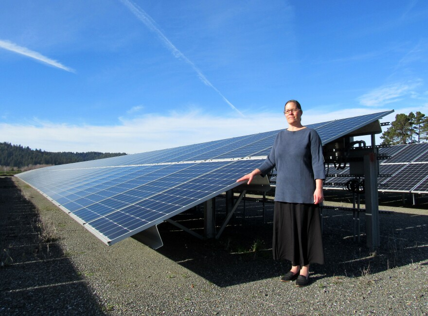 Photo of woman standing next to solar panels