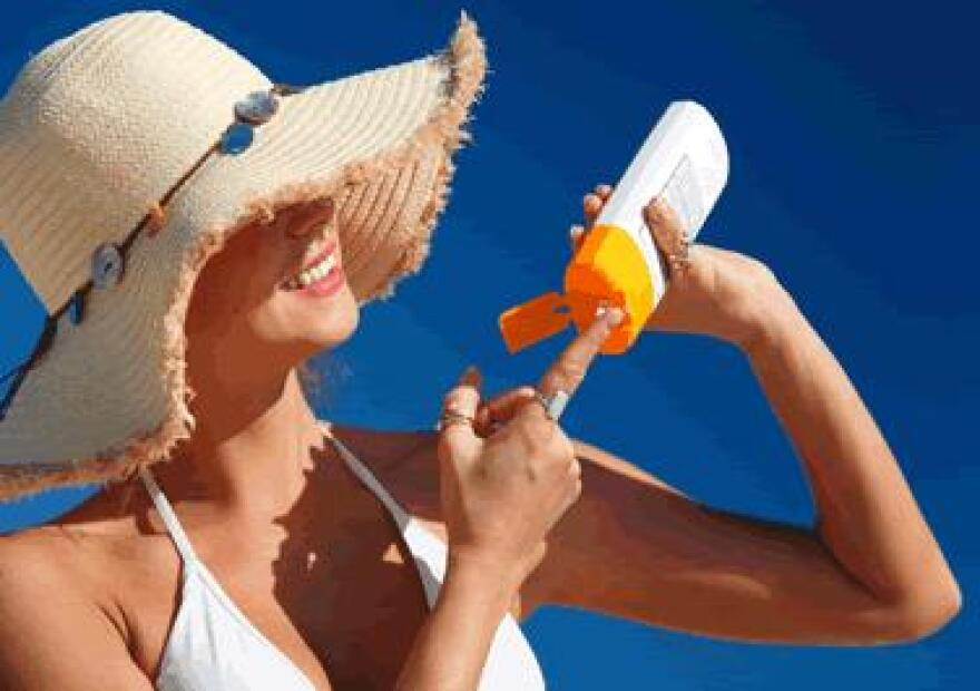 woman applies sunscreen