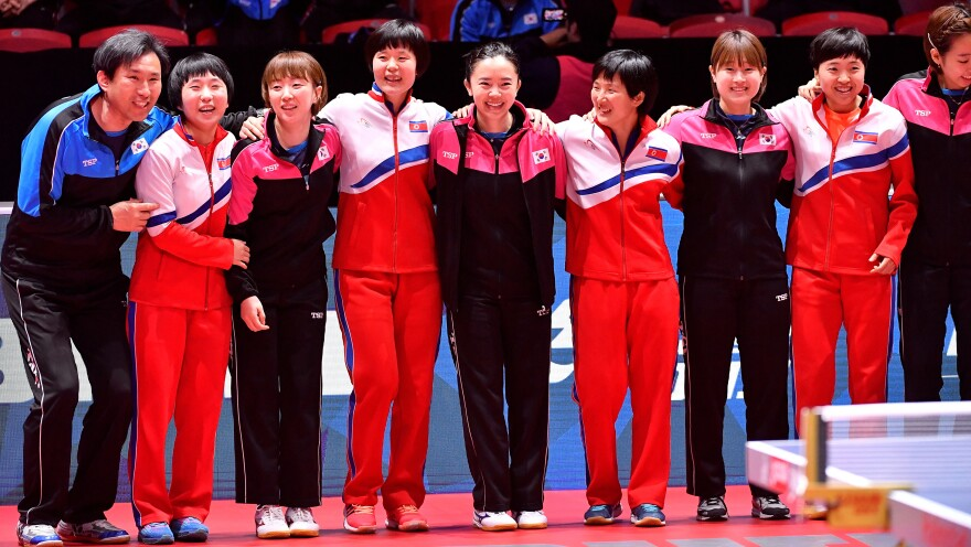 The South Korean and North Korean teams receive an ovation Thursday at the World Team Table Tennis Championships in Halmstad, Sweden. The players elected to form a unified Korean team for the tournament's semifinal round.
