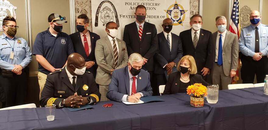 St. Louis Metropolitan Police Chief John Hayden, Mayor Lyda Krewson and other state and local leaders watch as Gov. Mike Parson signs legislation on Oct. 8, 2020 eliminating the residency requirement for public safety employees in St. Louis, including police officers.