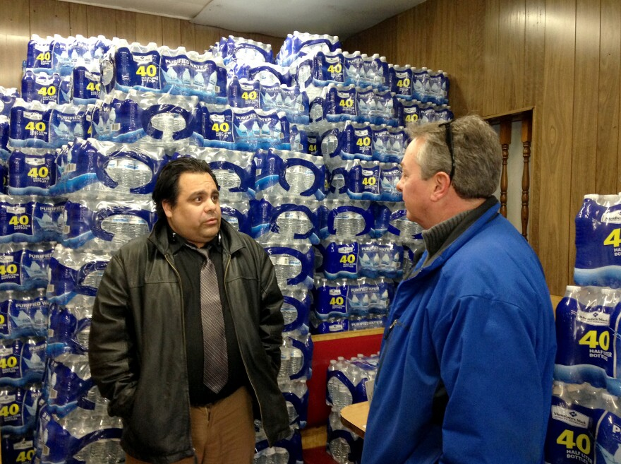 Carlos Amos, manager of Angelo's Coney Island in Flint, Mich., talks to Anthony Pavone, supervisor of the Genesee County Health Department. Amos says the restaurant's owner got a good deal on bottled water that customers can choose to buy.