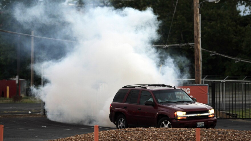 A car pulls away as tear gas is deployed by police in Ferguson, Mo., Monday, in an effort to quell unrest and looting in the wake of the death of teenager Michael Brown.
