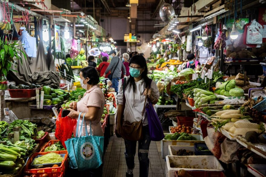 A woman walks through the wet markets wearing a protective face mask in Hong Kong.