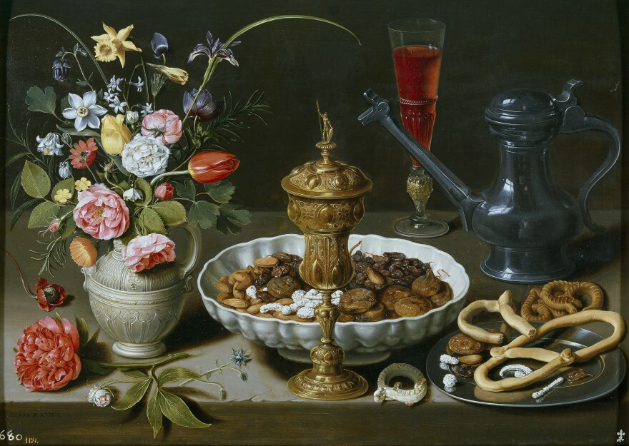 <em>Still life with Flowers, Gilt Goblet, Almonds, Dried Fruits, Sweets, Biscuits, Wine and a Pewter Flagon </em>was created by Clara Peeters in 1611.
