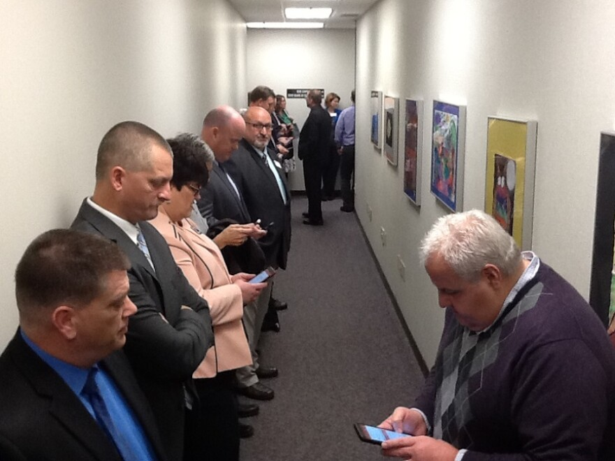 Dozens of school superintendents line the hallway outside a closed-door Missouri State Board of Education meeting Tuesday, Nov. 21, 2017 to show support for Commissioner Margie Vandeven.