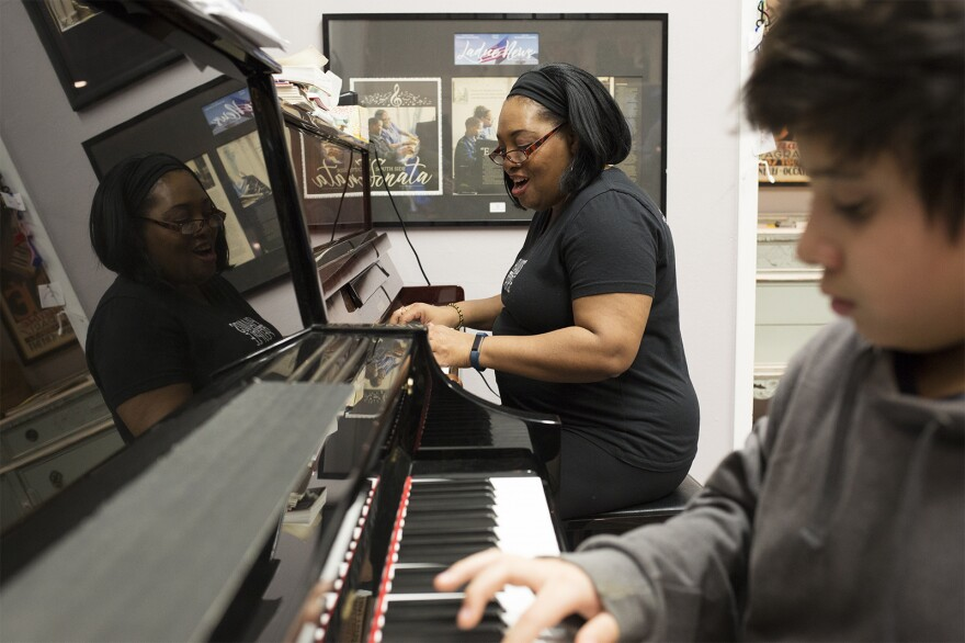 Students follow along as Kayia Baker, director of Pianos for People's piano school, leads a lesson for beginners.