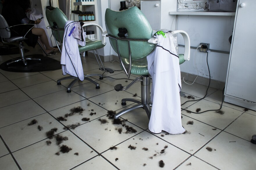 """Bits of a haircut lie on the floor before being swept up at OM Studio. NPR interviewed owner Om a few weeks after Hurricane Maria hit. """"I can't leave the island. I love this place and my clientele is here,"""" she said. Now business is booming at the salon."""