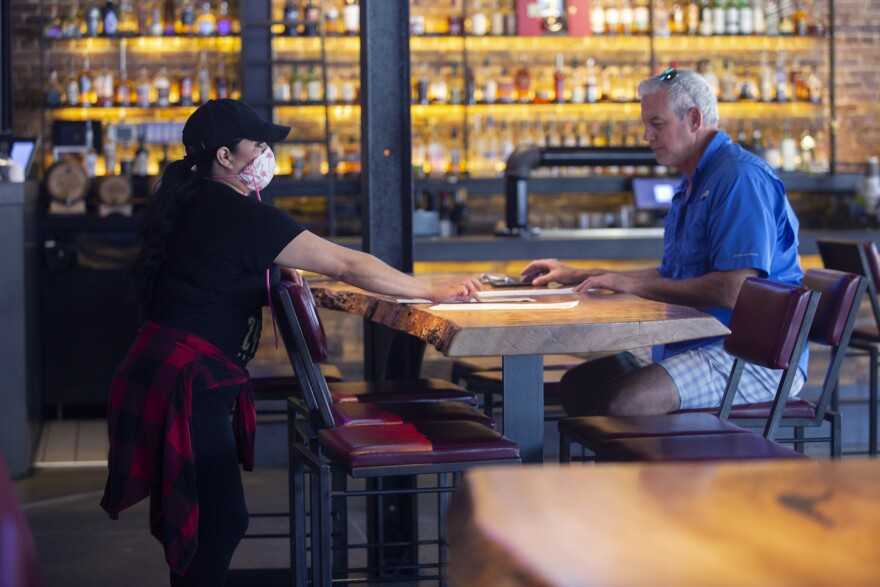 A masked waitress takes an order from an unmasked man at a restaurant