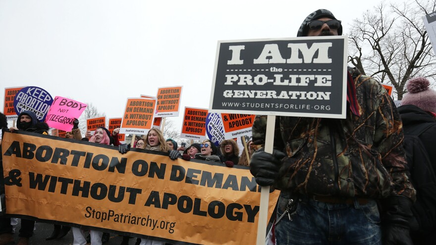 Protesters spread their dueling messages at a March for Life rally in 2016. Only 17 percent of Americans say they want the landmark <em>Roe v. Wade</em> ruling overturned, a new NPR/PBS NewsHour/Marist poll finds.