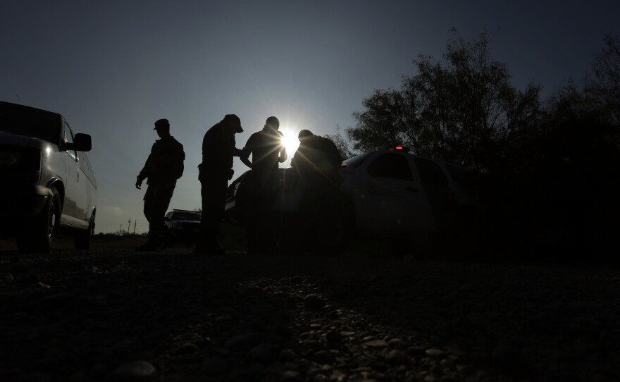 In this Nov. 6, 2019, file photo, Border Patrol agents apprehend a man thought to have entered the country illegally, near McAllen along the U.S.-Mexico border.