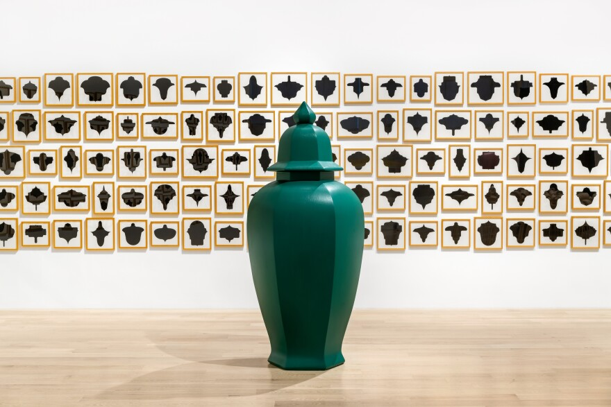 A green vase sculpture is placed in front of a drawing series by artist Allan McCollum.
