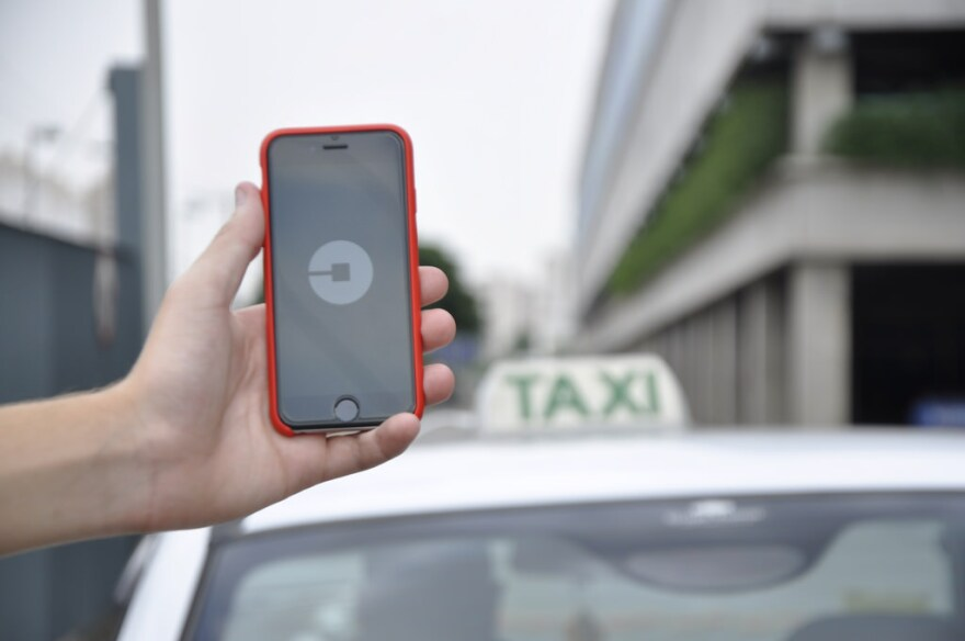 The Uber app being used in favor of a traditional taxi.