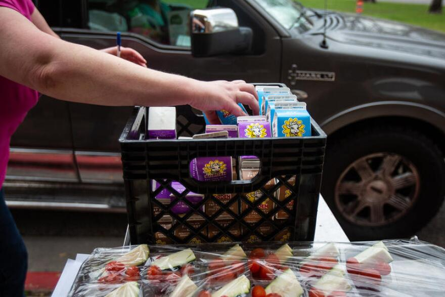 School employee grabs milk cartons from a basket during curbside meal distribution.