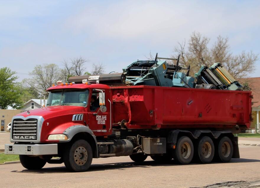 A dump truck hauls printing presses from The Garden City Telegram.