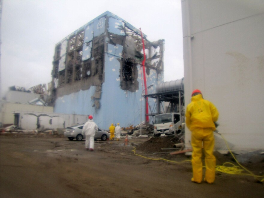 This file handout picture shows workers spraying water to cool down the spent nuclear fuel in the fourth reactor building at TEPCO's Fukushima Daiichi nuclear power plant.