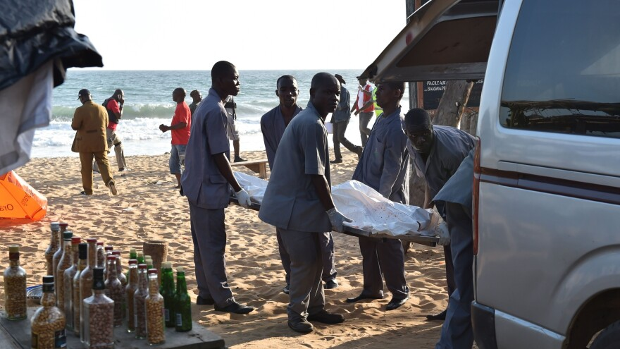 """Employees load a body into a van after heavily-armed gunmen opened fire in the Ivory Coast resort town of Grand-Bassam, leaving bodies strewn on the beach, killing more than a dozen people. The assailants, who were """"heavily armed and wearing balaclavas, fired at guests at the L'Etoile du Sud, a large hotel which was full of expats in the current heatwave,"""" a witness told AFP."""