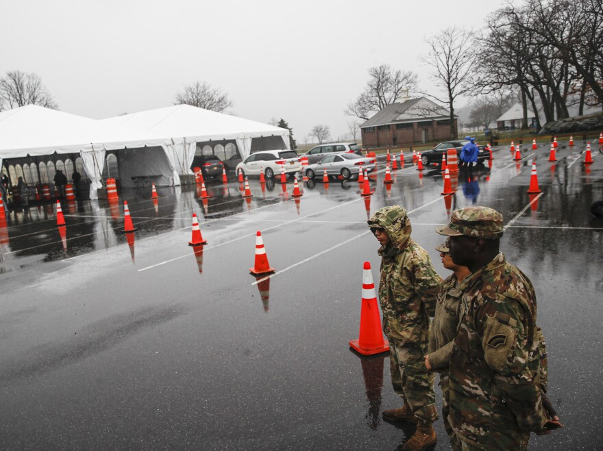 National Guard personnel stand beside a line of motorists waiting for COVID-19 coronavirus infection testing New Rochelle, N.Y., on Friday.