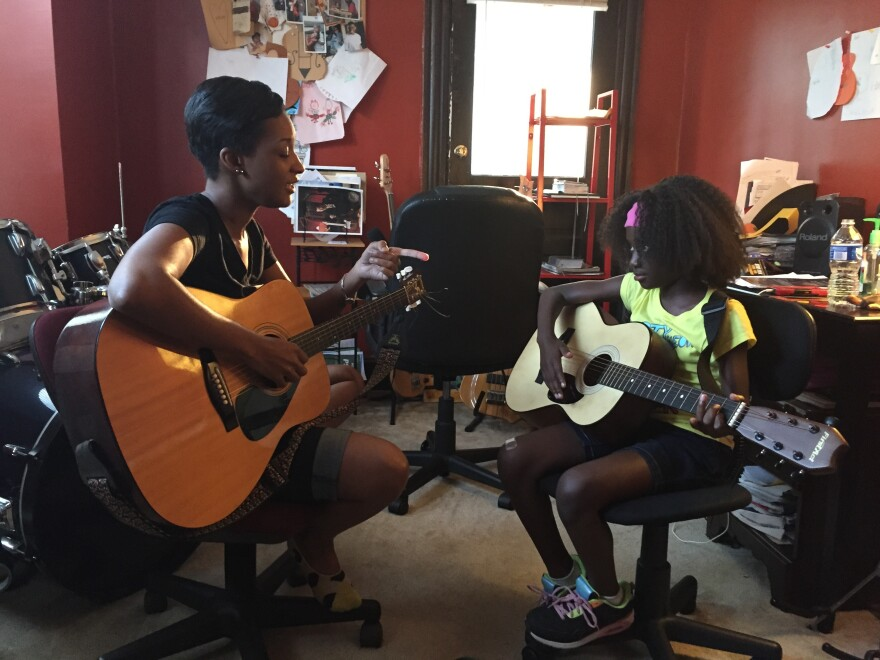 Tanesha Mitchell instructs her guitar student, 8-year-old Taniyah Winston, at her home in West Baltimore.