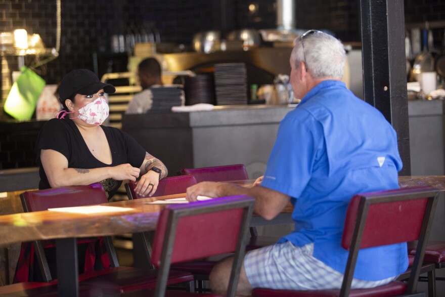 waitress wearing a mask speaks to a customer in a bar