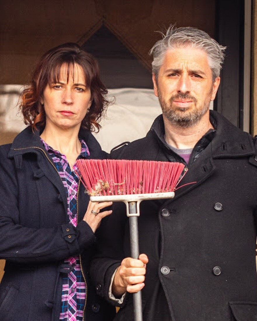 Photo of a man and woman posing in front of a house and holding a broom upside-down