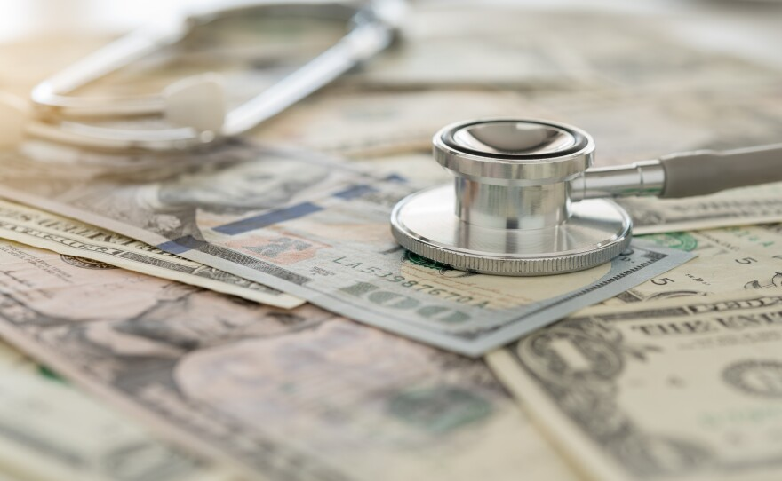 stethoscope resting on cash stock photo.