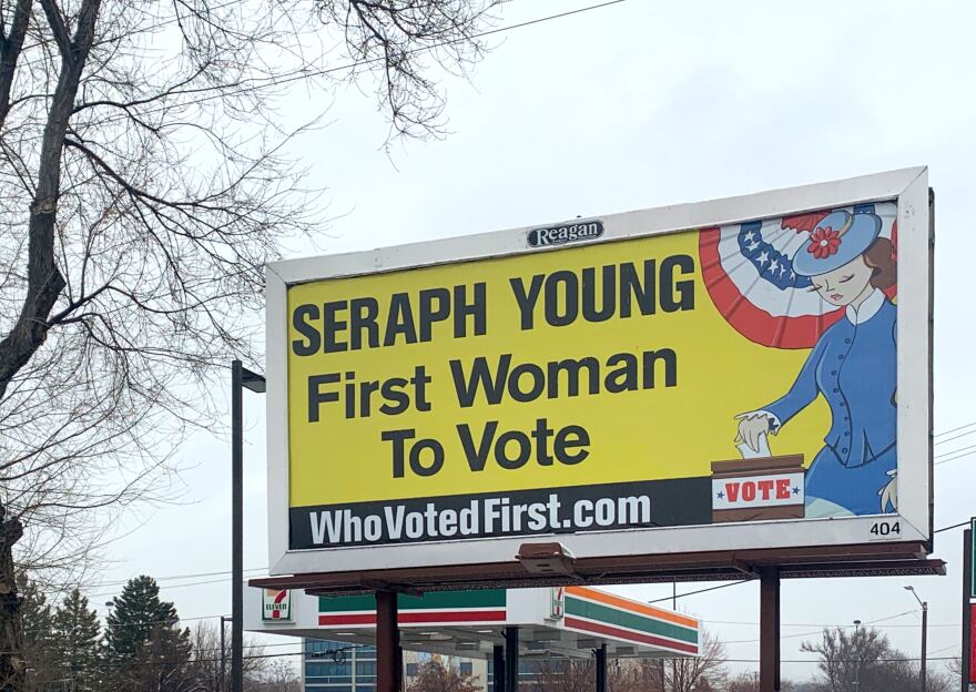"""Photo of billboard that reads """"Seraph Young, First Woman To Vote."""""""