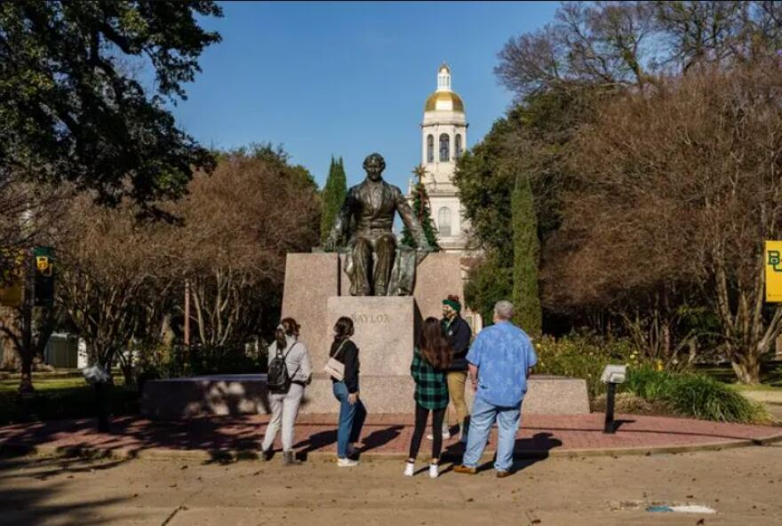 Prospective students on a campus tour pass in front of the statue of Judge Baylor at Baylor University in Waco.