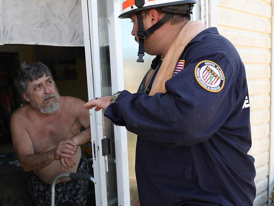 Brian Bartlett from the South Florida Search and Rescue team checks in on Tom Garcia, who stayed in his home through Hurricane Michael. Experts say people's decisions to stay are almost always carefully considered.