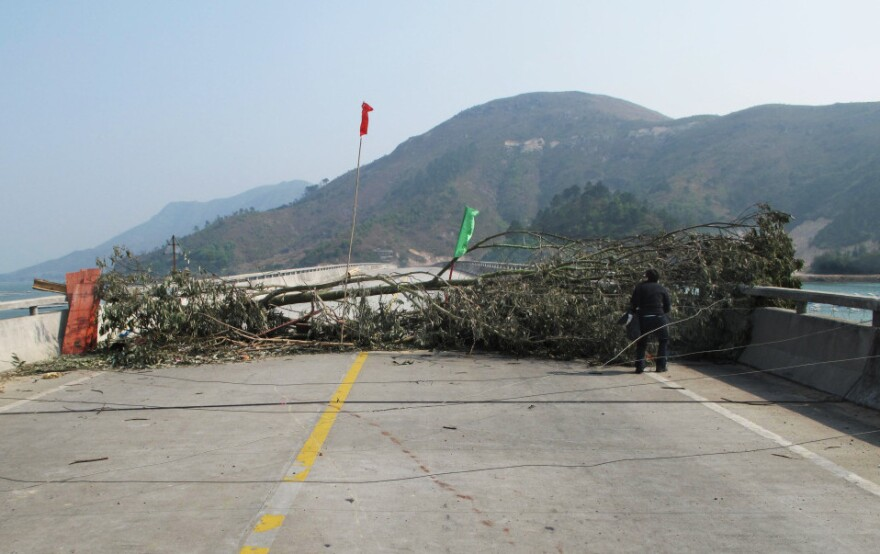 The Chinese national flag rises over villagers' barricades in Wukan. Tree trunks and broken glass are strewn in the road in an attempt to prevent authorities from moving in.